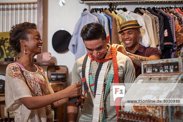 Drei Personen im Vintage-Laden  viele probieren gehäkelte Schals an