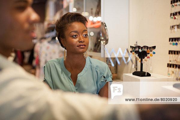 Junge Frau betrachtet Ohrringe im Vintage-Shop