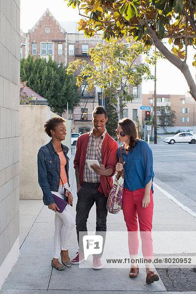 Drei Freunde auf dem Bürgersteig