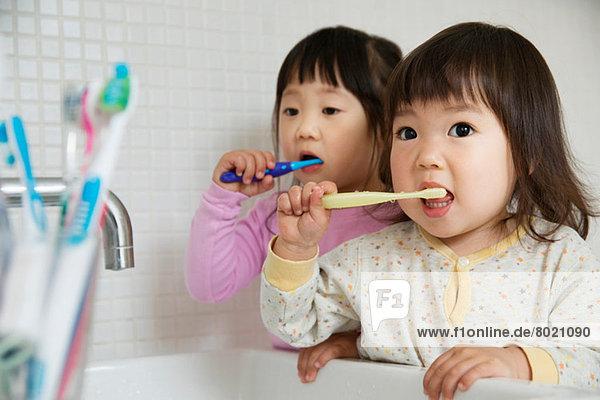 Zwei kleine Mädchen beim Zähneputzen am Waschbecken