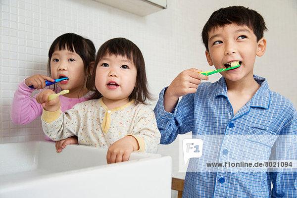 Brüder und Schwestern beim Zähneputzen