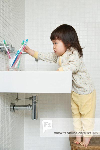 Mädchen-Kleinkind auf Zehenspitzen  das über das Waschbecken greift