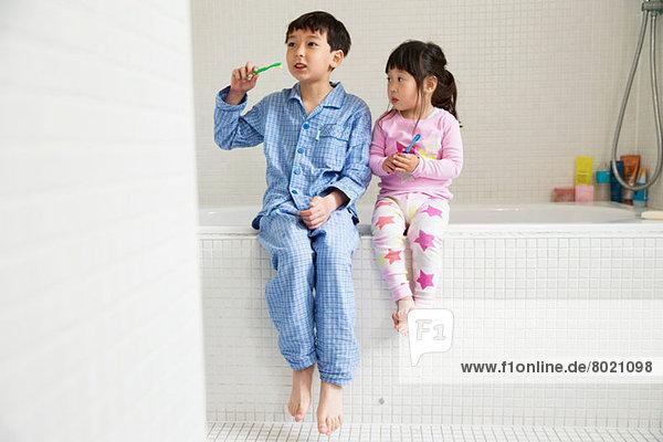 Bruder und Schwester sitzen mit Zahnbürsten auf dem Rand des Bades.