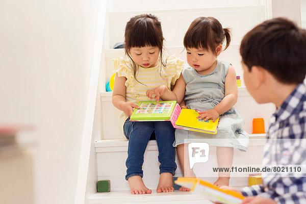 Weibliche Kleinkinder auf der Treppe mit Spielbuch