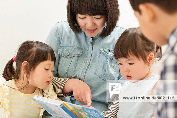 Mutter und Kinder beim Betrachten des Bilderbuchs