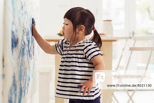 Weibliches Kleinkind beim Malen von Handabdrücken