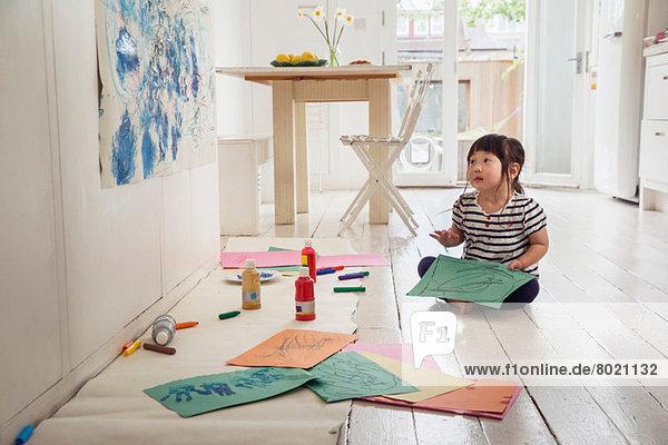 Kleinkind auf dem Boden sitzend mit Zeichnungen