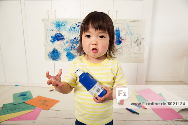 Weibliches Kleinkind mit Farbflasche