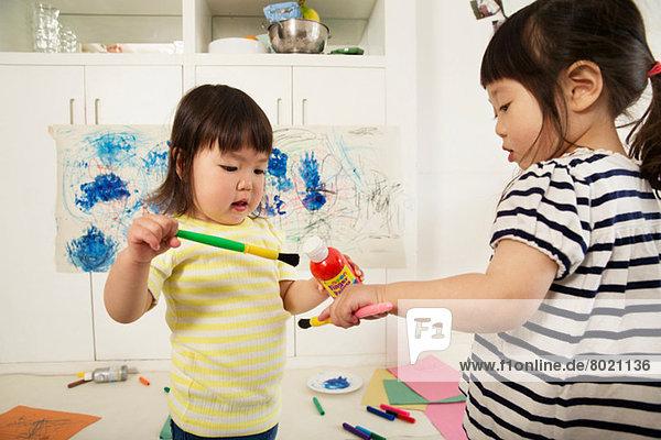 Zwei junge Schwestern mit Farbflasche und Pinsel