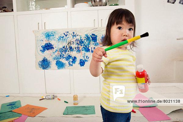 Weibliches Kleinkind mit Farbflasche und Pinsel