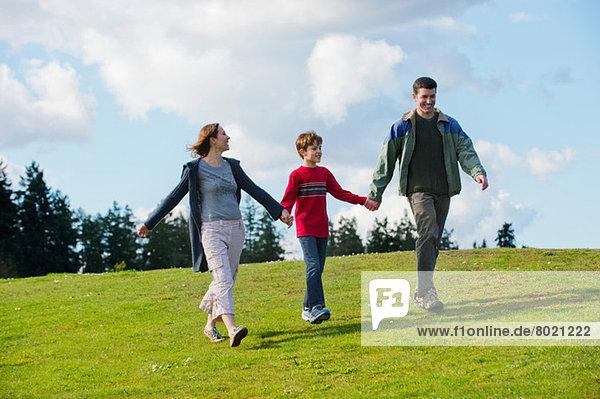 Eltern und Sohn gehen Hand in Hand