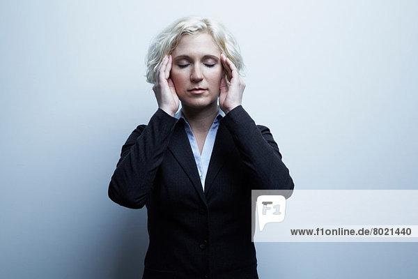 Studio-Porträt der Geschäftsfrau mit den Händen auf dem Gesicht