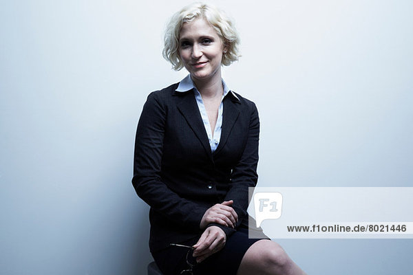 Studio-Porträt einer blonden Geschäftsfrau auf Hocker sitzend