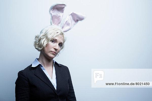 Studio-Porträt einer blonden Geschäftsfrau mit Hasenohren