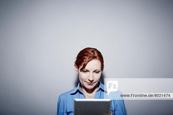 Studio-Porträt einer jungen Frau mit Blick auf das digitale Tablett