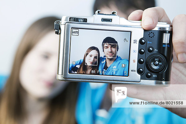 Couple taking pictures of themselves  self-portrait on the display of the camera