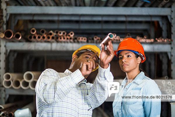 Zwei Lagerarbeiter schauen auf Kupferrohre