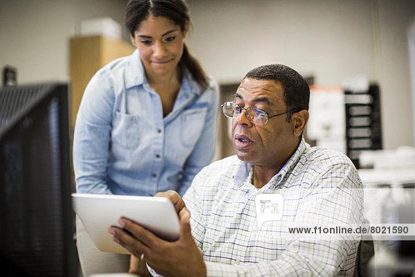Bürokollegen beim Betrachten des digitalen Tabletts
