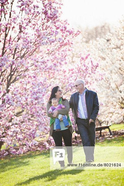 Großeltern und Enkelin beim Spaziergang im Park