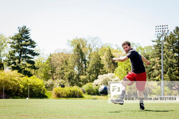 Fußballspieler beim Laufen und Treten des Balls