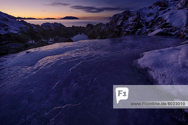 Fjord mit Eis und Felsen bei untergehender Sonne