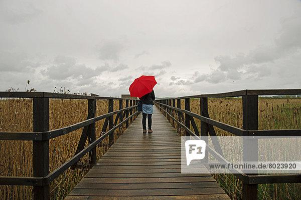 Frau mit rotem Regenschirm steht auf Holzsteg