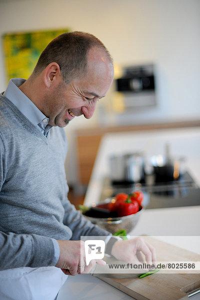A man is slicing a bell pepper.
