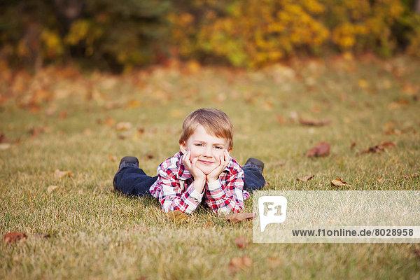 liegend  liegen  liegt  liegendes  liegender  liegende  daliegen  Portrait  Junge - Person  Herbst  jung  Gras