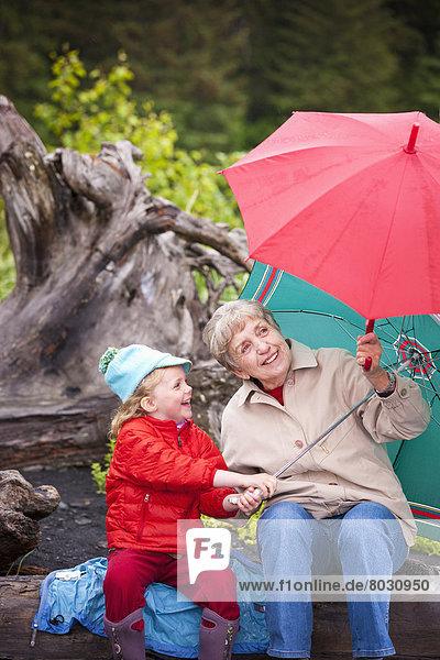 Vereinigte Staaten von Amerika  USA  sitzend  Tag  Spiel  Strand  Sommer  Regenschirm  Schirm  Regen  Enkeltochter  Großmutter  zeigen  Sonnenschirm  Schirm
