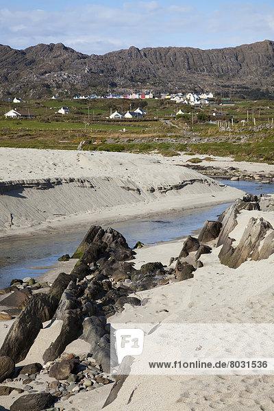 entfernt nahe Wasserrand Felsbrocken Gebäude weiß Sand Korken vorwärts Irland