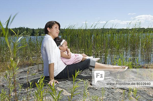 Felsbrocken  sitzend  nebeneinander  neben  Seite an Seite  Fischschwarm  See  1  Tochter  Schilf  Ethnisches Erscheinungsbild  Mutter - Mensch  Kanada  alt  Ontario  Jahr