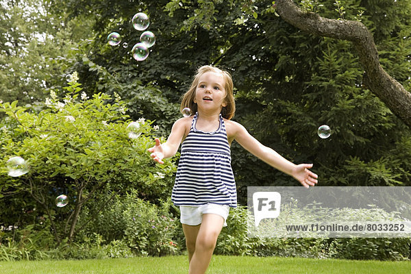 Young Girl Chasing Floating Bubbles  Ontario Canada