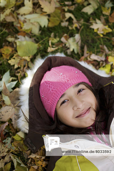 Middle Eastern Girl Lying In Autumn Leaves Outside Esl School  Guelph Ontario Canada
