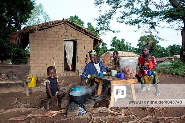 family in front of their house in central african republic.