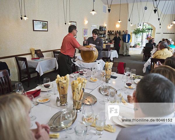 Cutting block of parmesan cheese in Italian restaurant  II Bisto  Grand Junction  Colorado  USA