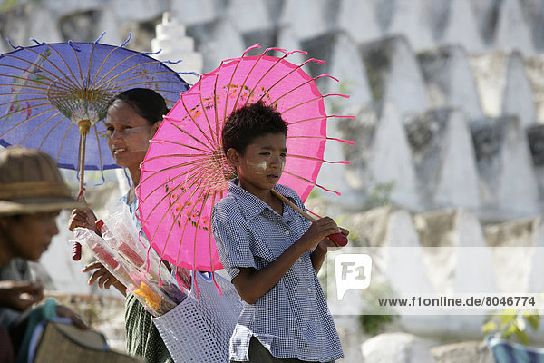 Local people with parasols in front of stupas  Burma