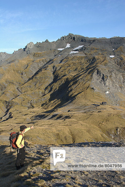Man pointing to new chalet on Dragonfly Peak in Southern Alps  New Zealand