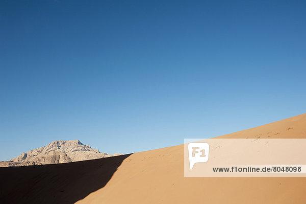 Sandy desert with mountain in background  Jordan