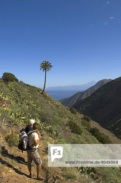 Tourist hiking near on Vallehermoso trail with island of Tenerife in background   La Gomera  Canary Islands  Spain