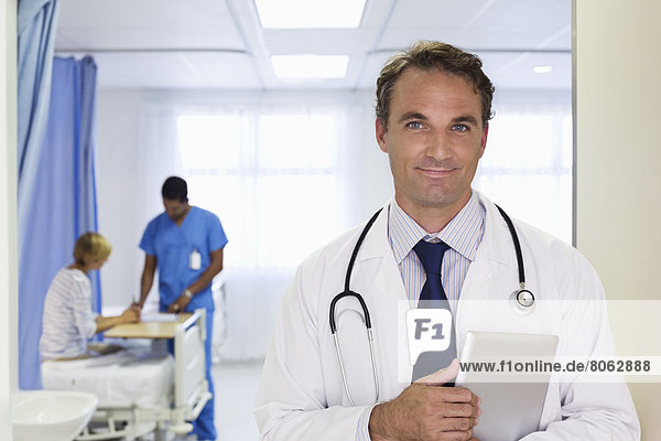 Doctor carrying tablet computer in hospital
