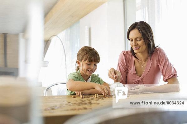 Mutter und Tochter füllen Spardose