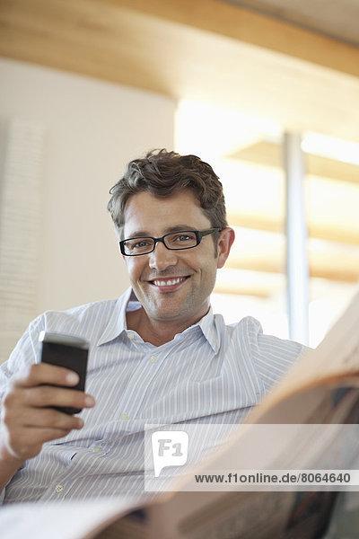 Mann mit Handy auf dem Sofa