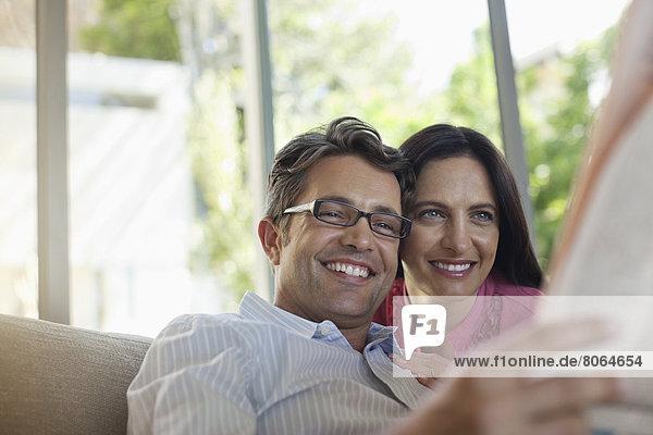 Paar liest Zeitung zusammen auf dem Sofa