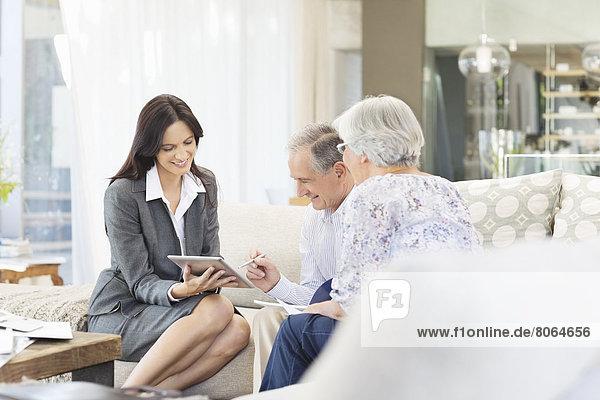 Finanzberater mit Tablet-Computer bei Kunden