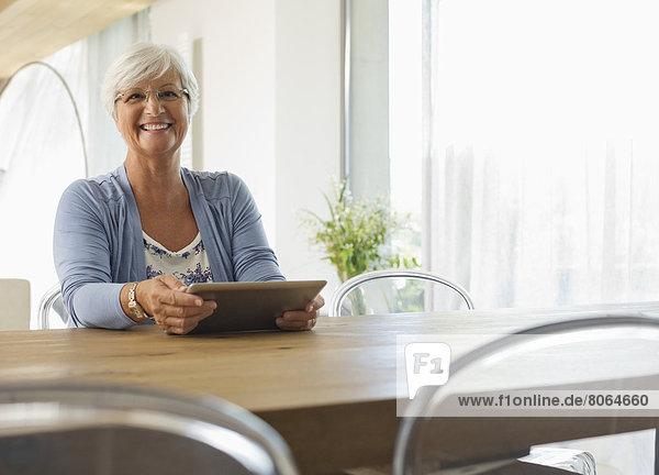 Ältere Frau mit Tablet-Computer am Tisch