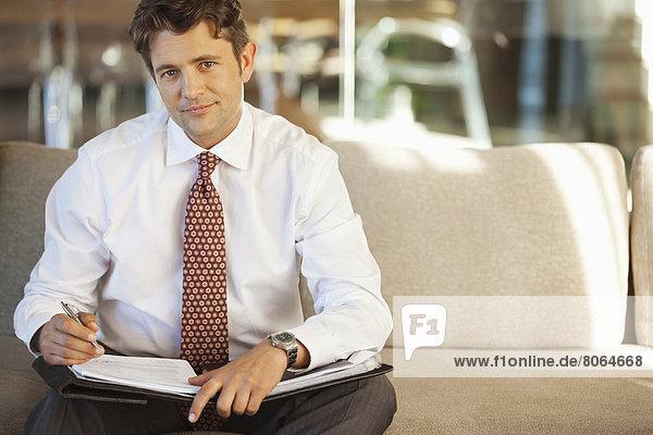 Geschäftsmann beim Notieren auf dem Sofa