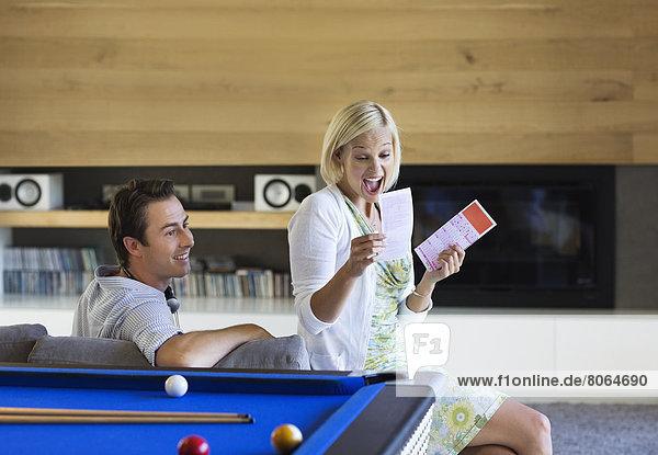 Pärchen  die Lotterielose auf dem Sofa prüfen