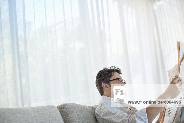 Mann liest Zeitung auf Sofa