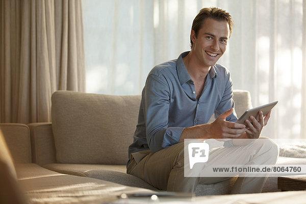 Mann mit Tablet-Computer auf dem Sofa