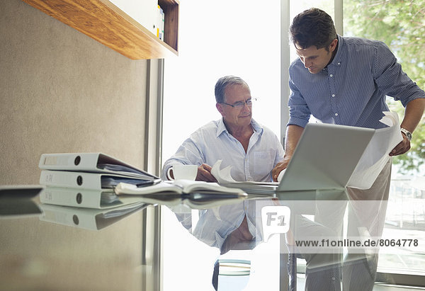 Älterer und jüngerer Mann beim Reden am Schreibtisch